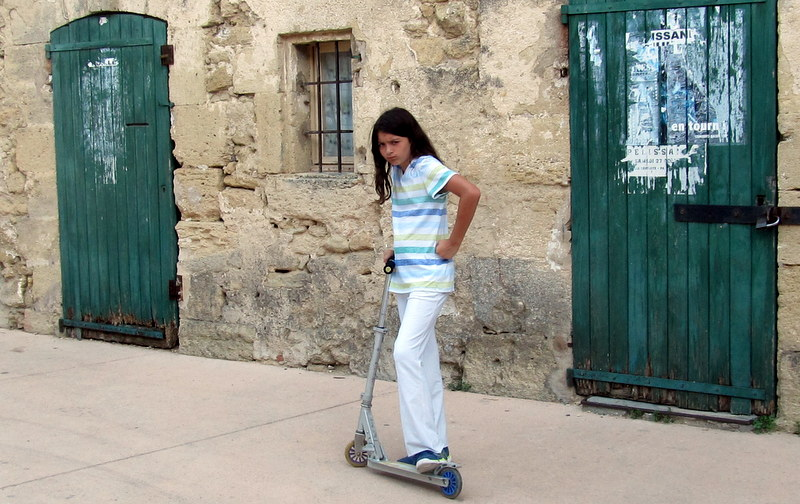 "My daughter, showing off ""her attitude"" while she scoots around our picturesque village."